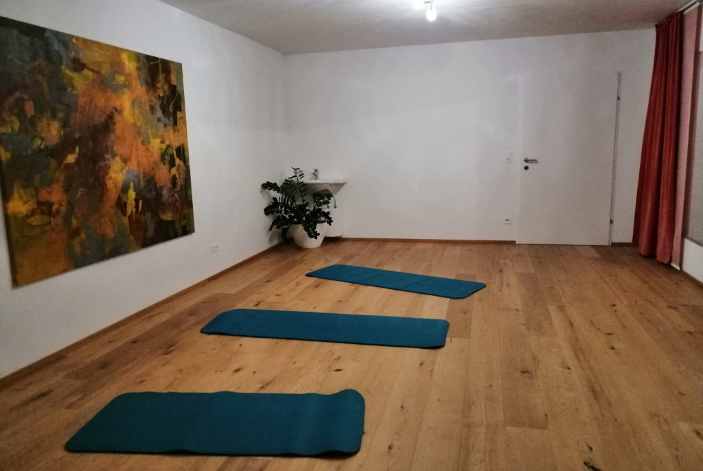 Pilatesraum, Holzboden, Matten, Wandbild